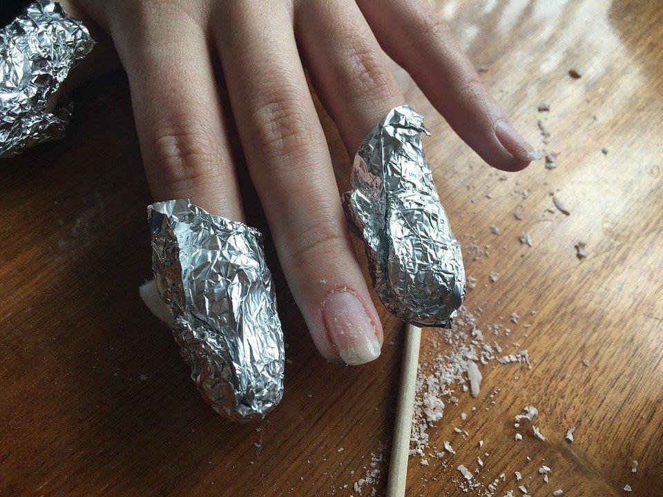 Aplicando quitaesmalte para eliminar la tiña en las uñas.